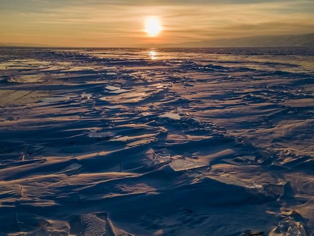 Великолепный закат над замерзшим озером байкал замерзшие куски льда на поверхности озера россия