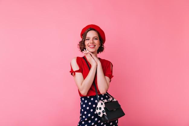Magnifica ragazza bianca in abito glamour in posa. gioconda donna francese in berretto in piedi con un sorriso carino.