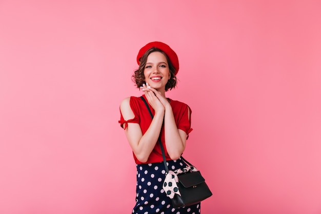 華やかな衣装でポーズをとる壮大な白人の女の子。かわいい笑顔で立っているベレー帽のjocundフランス人女性。