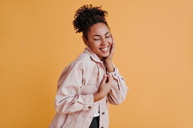 Великолепная женщина в куртке смеется с закрытыми глазами
