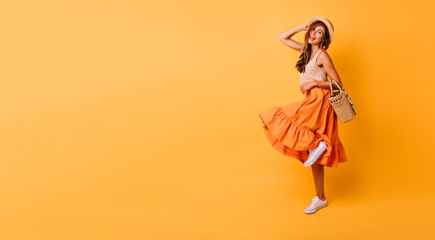 Magnificent woman in long bright skirt dancing in studio. carefree inspired female model posing with pleasure on yellow.