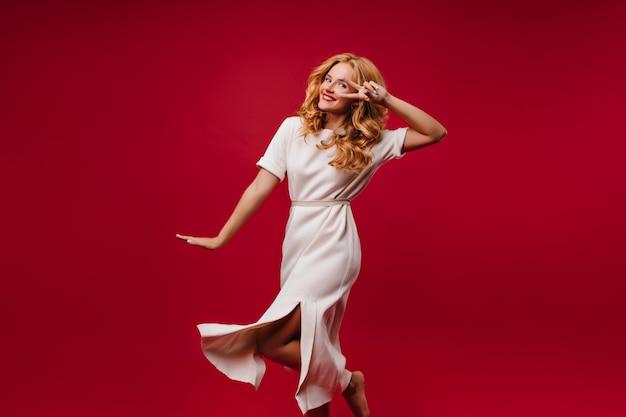 Magnifica donna in abito bianco che esprime felicità. adorabile ragazza bionda che balla sulla parete rossa.