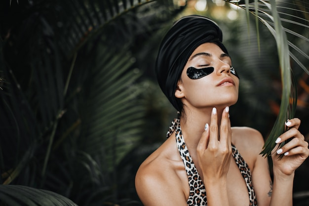 Magnificent woman with eye patches touching chin. european woman in black turban posing on exotic background.