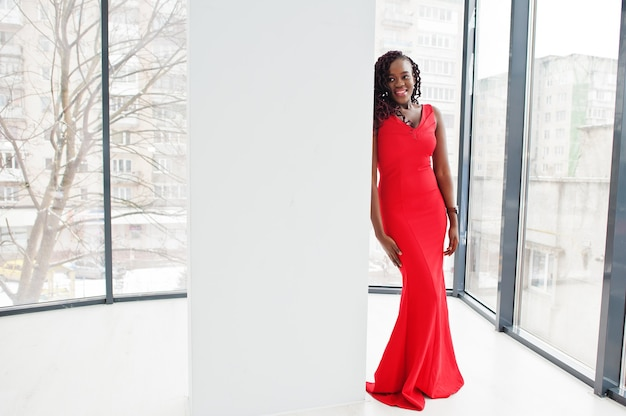 豪華なアパートで豪華な赤いドレスを着た壮大な若いアフリカの女性。美容、ファッション。