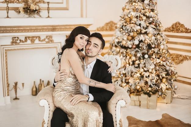 크리스마스를 위해 장식 된 고급 인테리어에 세련된 의상을 입은 웅장한 젊은 부부.