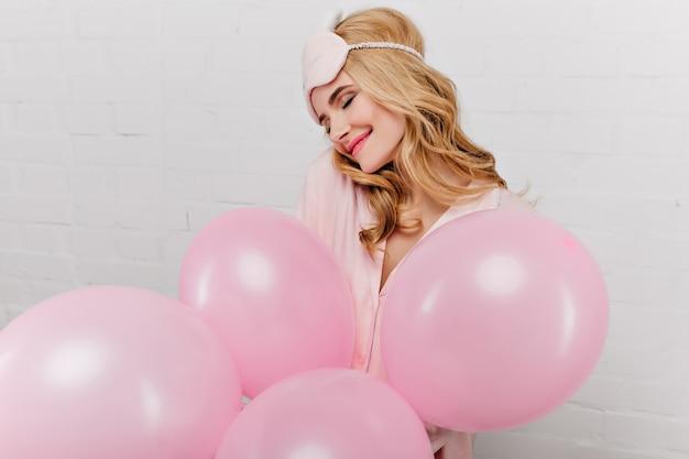 헬륨 풍선을 들고 기쁨과 함께 포즈 핑크 eyemask에 웅장 한 젊은 여자. 아침에 그녀의 생일을 축하하는 멋진 소녀의 실내 초상화.