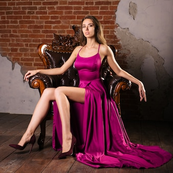 Magnificent young woman in luxurious dress is sitting in a chair