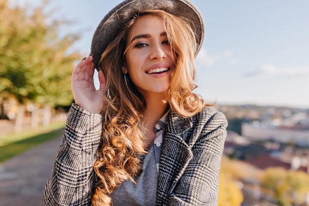 Magnifica giovane donna con bellissimi occhi azzurri in posa in cappello su sfocatura dello sfondo della città