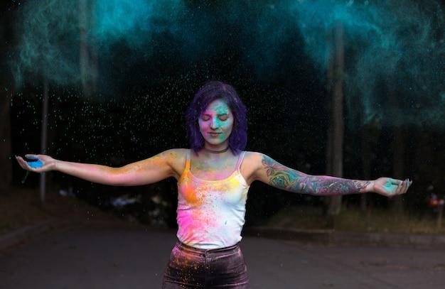 カラフルなホーリーパウダーを投げる紫色の髪の壮大な若い女性