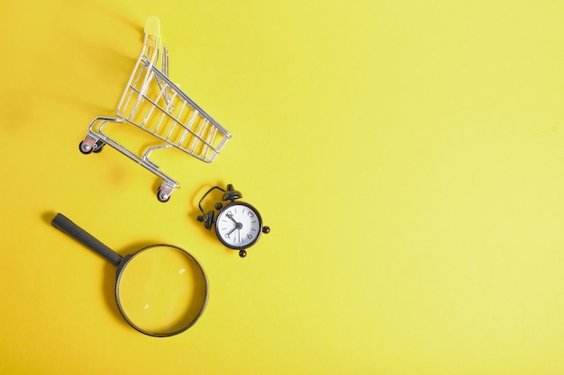 Magnifier, alarm clock and miniature shopping basket on yellow background top view copy space
