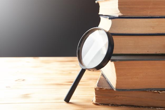 拡大鏡とテーブルの上の本。本の研究の概念