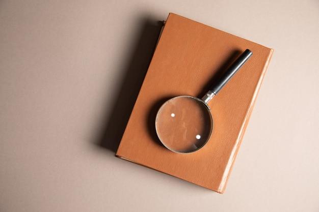 Лупа и книги на столе. концепция изучения книги