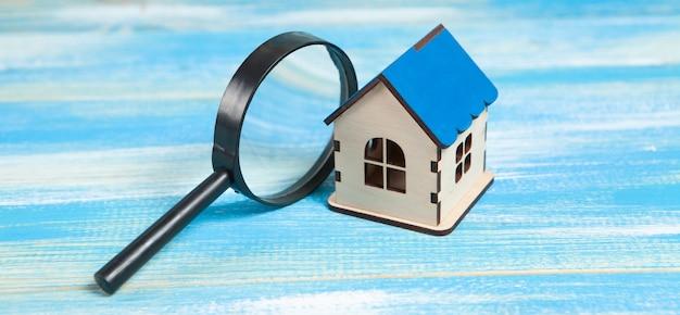 돋보기와 집. 홈 검색 개념. 파란색 테이블에 가정 검사