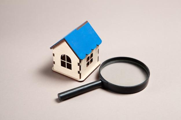 ピンクの背景に拡大鏡と家。家探しのコンセプト