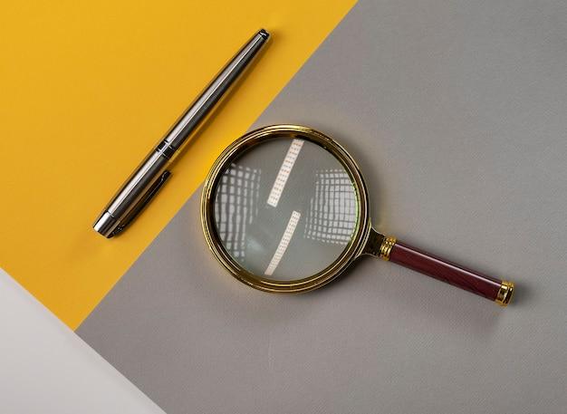 灰色と黄色のテーブルに拡大鏡とペン。