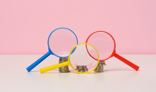 テーブルの上の拡大鏡と白いコイン。所得成長の概念、投資の高い割合。新しい収入源、補助金を探す