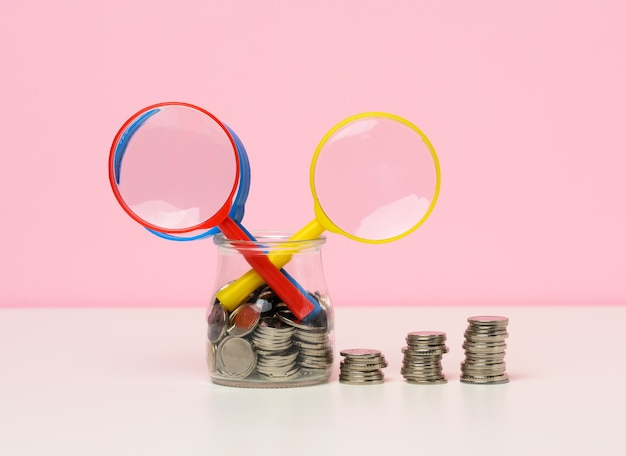 テーブルの上の拡大鏡と白いコイン。収入成長の概念、投資の高い割合。新しい収入源、補助金を探す