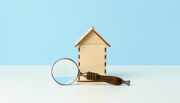 돋보기와 파란색 배경에 목조 주택입니다. 부동산 임대, 구매 및 판매 개념입니다. 부동산 서비스, 건물 수리 및 유지 보수