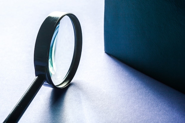 Magnifier on blue surface close up