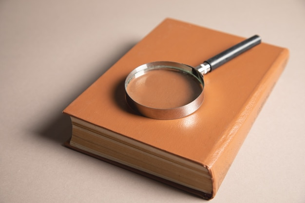 Magnifier and books on the table. book study concept
