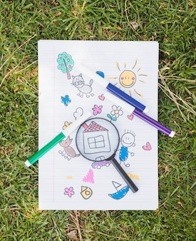 Magnifier on childish drawing on grass