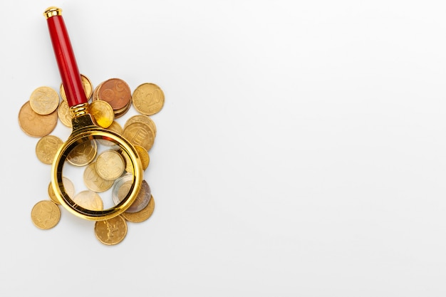 Magnifier and coins on white background