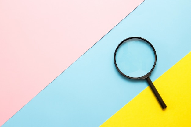 Magnifier on colored paper. top view. search concept