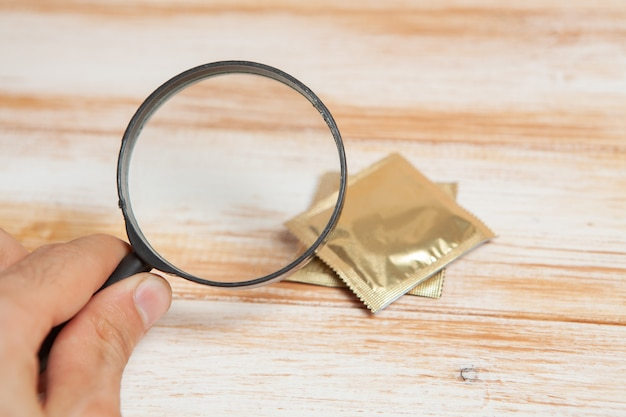 Magnifier and condom on wooden table