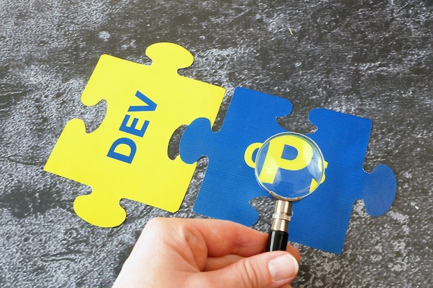 단어 dev 및 ops 퍼즐이있는 돋보기 유리. 소프트웨어 엔지니어링 문화 및 실습, 근접 촬영에 대한 개념