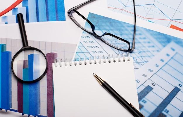 Лупа, очки, белый блокнот и ручка на ярких схемах. на рабочем месте крупным планом