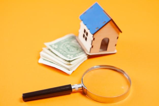 돋보기, 집과 노란색 표면에 돈. 집 비용 연구 개념