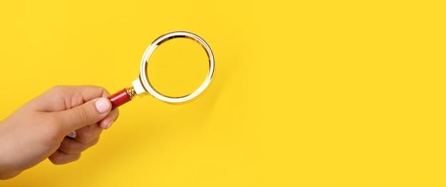 노란색 배경, 파노라마 이미지 위에 손에 돋보기