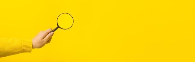 黄色の背景、パノラマのモックアップ画像の上に手に拡大鏡
