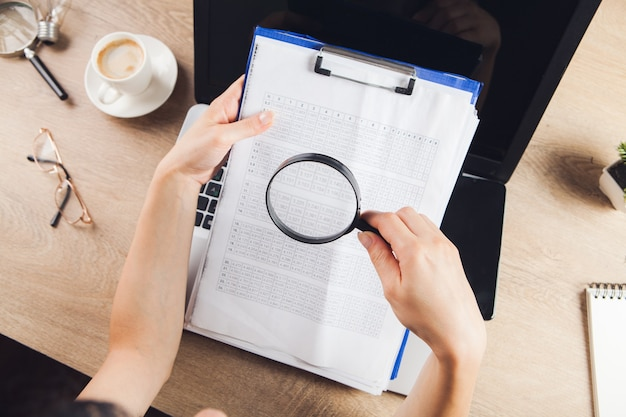 Magnifier looks at paper in front of laptop