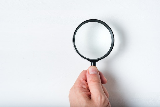 Magnifier in a man's hand on a white background.