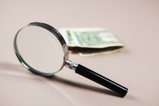 Magnifier and money on white surface