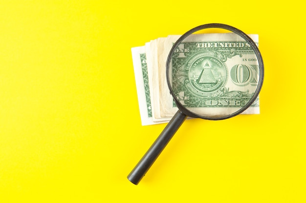 Magnifier and money on a yellow scene