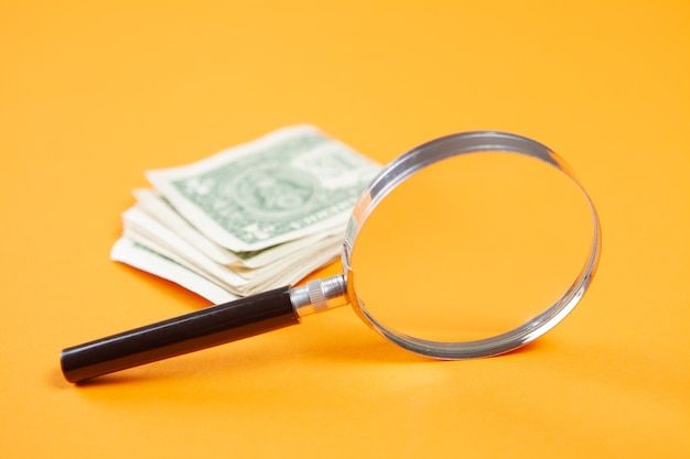 Magnifier and money on a yellow surface