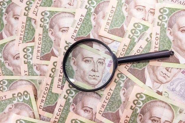 Лупа на фоне гривны. украинские деньги. 500 гривен. проверяйте деньги с помощью лупы.