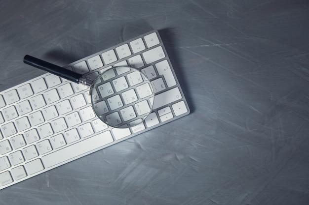 테이블에 컴퓨터 키보드에 돋보기