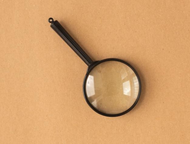 갈색 판지 배경 위에 돋보기 또는 돋보기 렌즈. 검색 도구.