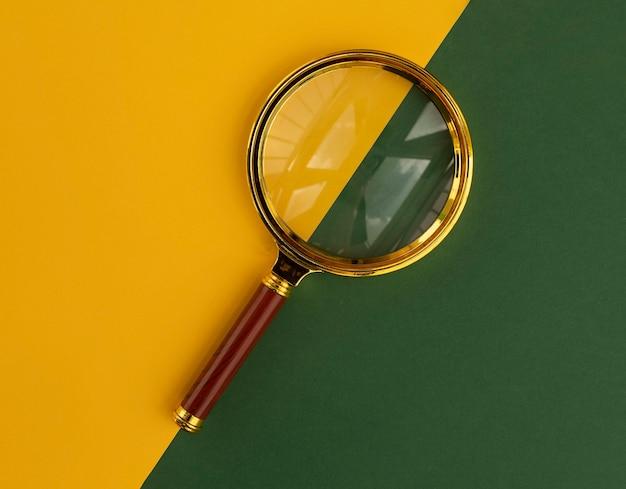 Лупа на желтом и зеленом фоне. инструмент поиска.
