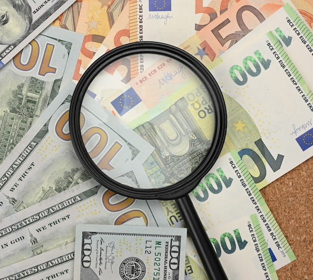 Magnifier and paper euro and dollar bills. analysis of exchange rate fluctuations