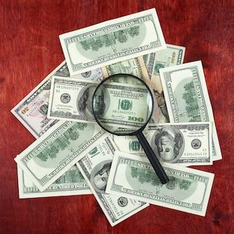 お金のドルと木の背景のビジネスコンセプトの中心に配置された拡大鏡