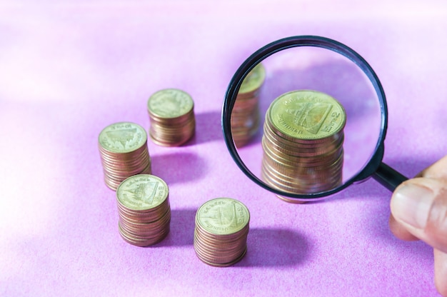 Magnifier searching investment of stacking coin growing on pink background