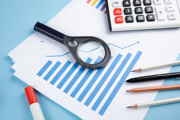 파란색 테이블에 돋보기, 통계 및 계산기