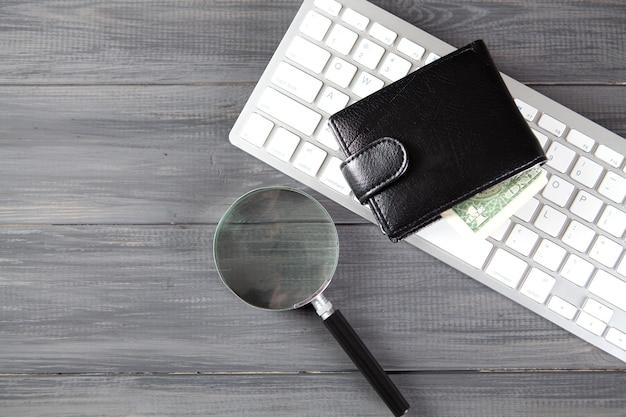 灰色の木製テーブルに拡大鏡、財布、キーボード。オンライン資金調達の概念