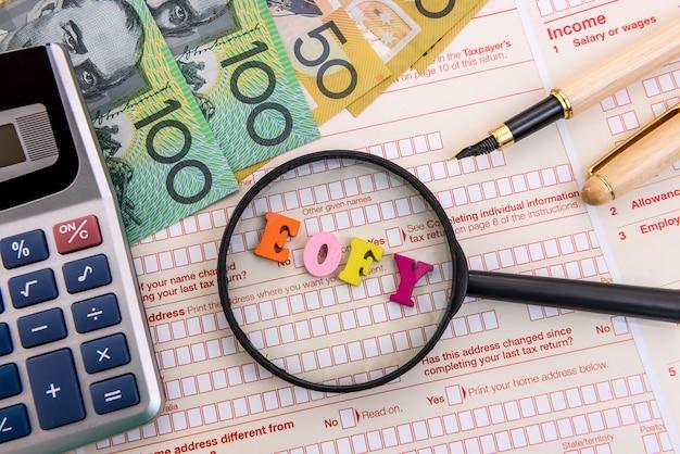 Лупа с австралийскими долларами и калькулятором в налоговой форме