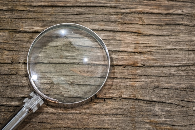 Magnifier on the wooden table with copy space