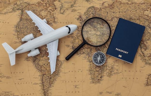 古い地図上の虫眼鏡と飛行機、コンパス、パスポート。旅行、冒険の概念